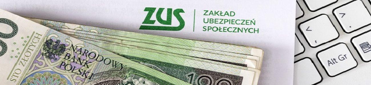 Banknoty o nominale 100 złotych leżą na kopercie z logo ZUS oraz klawiaturze